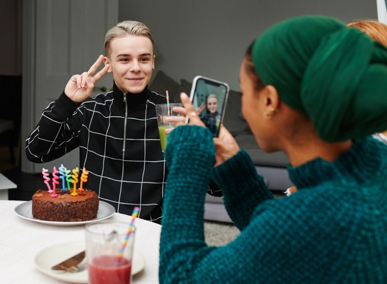 A woman taking picture of a friend with a birthday cake to backup to Shutterfly