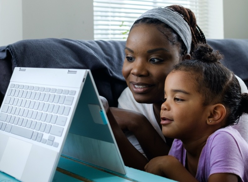 A mom and her daughter looking at a tablet organizing their photos with Shutterfly