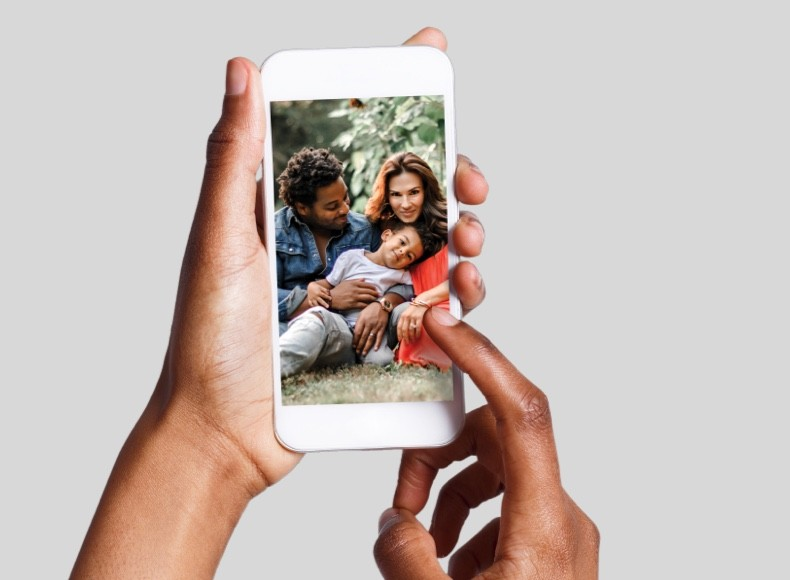 Hands holding a smartphone and showing a family photo