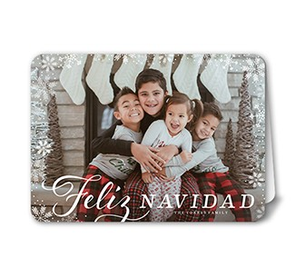 Custom Tarjeta de Navidad with a photo of four kids in front of the fire place and stockings