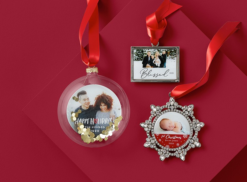 A cube personalized Christmas ornament with pictures of a family and a truck carrying a Christmas tree
