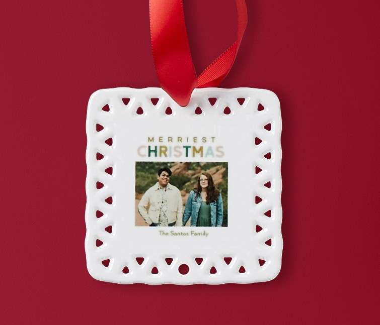 A white personalized ceramic ornament that says Merriest Christmas with a picture of a couple
