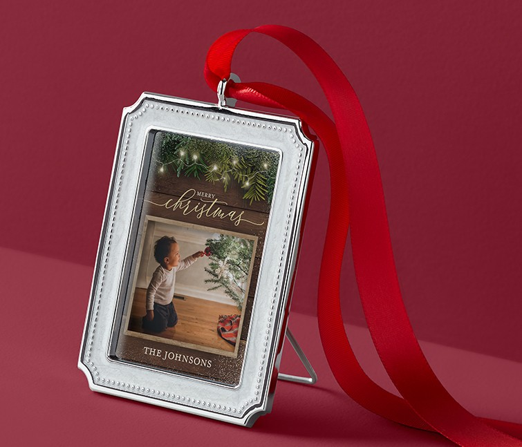 A personalized picture frame ornament that says Merry Christmas with a picture of a child touching a Christmas tree