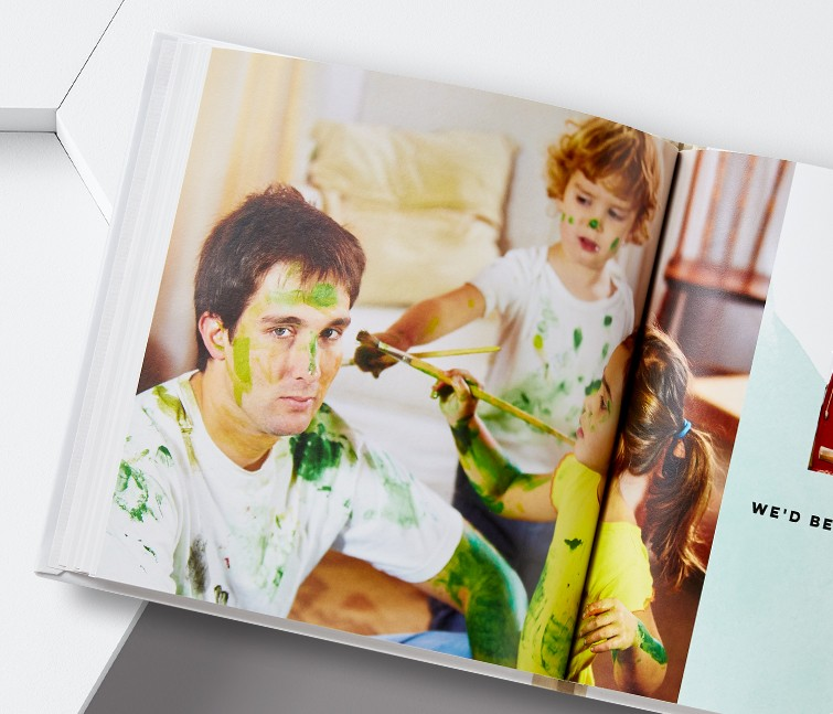 An everyday custom photo book with a picture of kids painting their dad