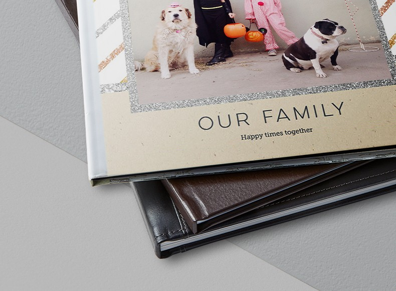 A stack of hardcover and leather photo books with a picture of a family and dogs on the cover