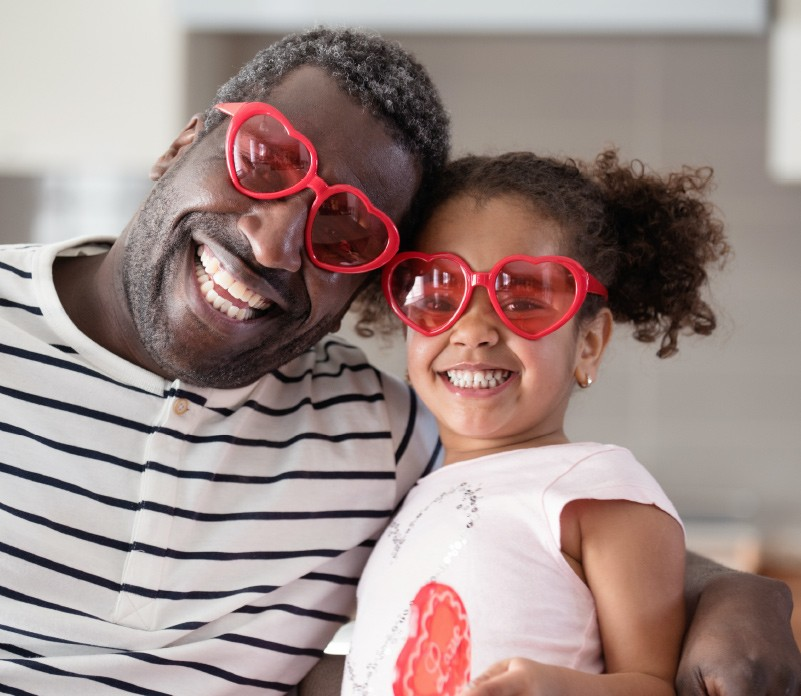 Grandpa and granddaughter celebrate Valentine's Day with heart-shaped glasses.