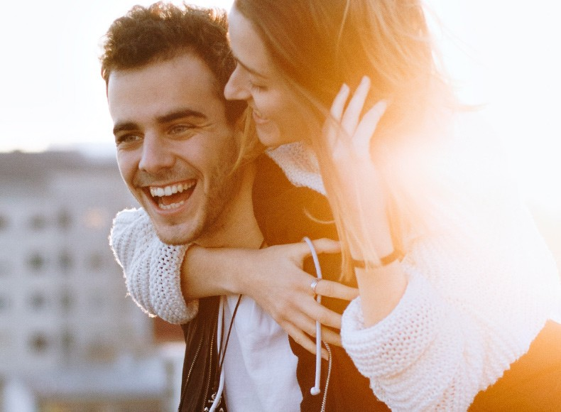 Girlfriend and boyfriend laugh together as they celebrate their love.