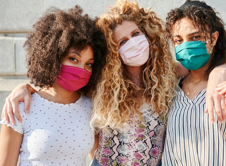 Three friends celebrate Galentine's Day together in custom masks.